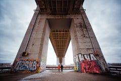 Pares jovenes por la tarde debajo del puente Fotografía de archivo libre de regalías