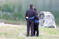 Pares jovenes por un lago Fotos de archivo libres de regalías