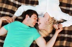Pares jovenes preciosos en el amor que descansa sobre la tela escocesa Fotos de archivo libres de regalías