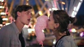 Pares jovenes preciosos en el parque de atracciones Pasando el tiempo junto, comiendo el caramelo de algodón rosado de lados Pare metrajes