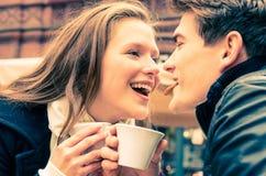 Pares jovenes preciosos gozando de una taza de café fotografía de archivo