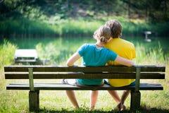 Pares jovenes preciosos que se sientan en banco Foto de archivo libre de regalías