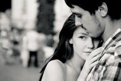 Pares jovenes que abrazan blando en muchedumbre Foto de archivo libre de regalías