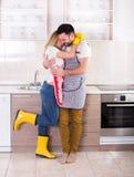 Pares jovenes que abrazan después de quehacer doméstico fotografía de archivo