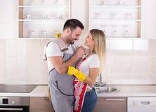 Pares jovenes que abrazan después de quehacer doméstico foto de archivo