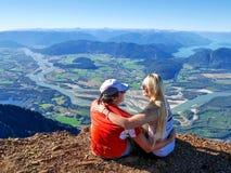 Pares jovenes que abrazan en el acantilado con una hermosa vista Imagen de archivo libre de regalías