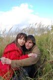 Pares jovenes que abrazan en el campo. Foto de archivo libre de regalías