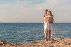 Pares jovenes que abrazan en el mar Foto de archivo libre de regalías