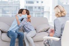 Pares jovenes que abrazan en el sofá Foto de archivo