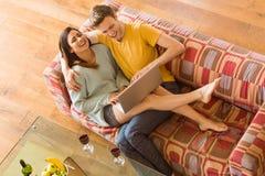 Pares jovenes que abrazan en el sofá con el ordenador portátil Fotos de archivo