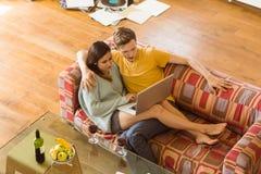 Pares jovenes que abrazan en el sofá con el ordenador portátil Foto de archivo libre de regalías