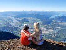 Pares jovenes que abrazan en el top de la montaña foto de archivo