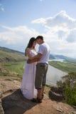 Pares jovenes que abrazan en montañas Fotografía de archivo