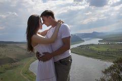 Pares jovenes que abrazan en montañas Foto de archivo libre de regalías