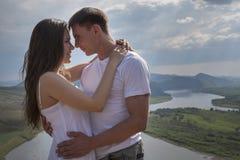 Pares jovenes que abrazan en montañas Fotografía de archivo libre de regalías