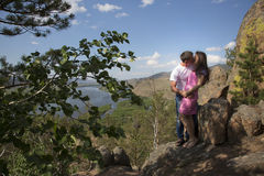 Pares jovenes que abrazan en montañas Imagen de archivo libre de regalías