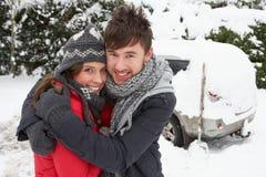 Pares jovenes que abrazan en nieve con el coche Fotos de archivo