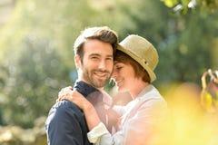 Pares jovenes que abrazan en parque Imagen de archivo libre de regalías