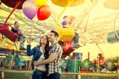 Pares jovenes que abrazan en parque de atracciones Foto de archivo libre de regalías