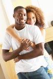 Pares jovenes que abrazan en sala de estar Fotografía de archivo