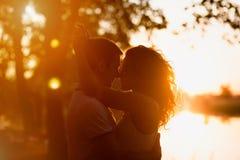 Pares jovenes que abrazan en un fondo blanco de una puesta del sol Imagenes de archivo