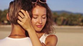 Pares jovenes que abrazan junto en la playa metrajes