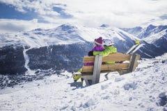 Pares jovenes que abrazan las montañas del invierno de la estación de esquí Imagenes de archivo