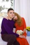 Pares jovenes que abrazan sentarse en el cuarto Imagen de archivo libre de regalías