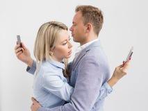 Pares jovenes que abrazan y aún usando sus teléfonos móviles Imágenes de archivo libres de regalías