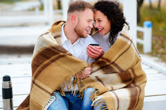 Pares jovenes que abrazan y cubiertos con un o que se sienta combinado caliente Imágenes de archivo libres de regalías