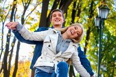 Pares jovenes que abrazan y que ligan en parque Foto de archivo libre de regalías