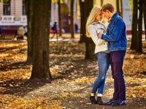 Pares jovenes que abrazan y que ligan en parque Fondo de la ciudad del otoño imagen de archivo libre de regalías