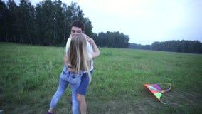 Pares jovenes que abrazan y que se besan en campo del verano almacen de metraje de vídeo