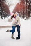 Pares jovenes que abrazan y que se besan en el parque en invierno Fotografía de archivo