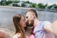 Pares jovenes que abrazan y que sonríen en uno a en el riverbank El caminar a lo largo de la playa arenosa Haga Selfies fotografía de archivo libre de regalías