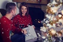 Pares jovenes que abren un regalo de Navidad Imagen de archivo libre de regalías