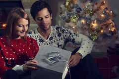 Pares jovenes que abren un regalo de Navidad Fotos de archivo