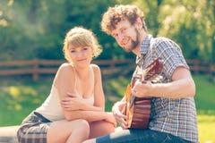 Pares jovenes que acampan tocando la guitarra al aire libre Imagen de archivo libre de regalías
