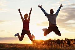 Pares jovenes que activan en los suberbs después de puesta del sol imagen de archivo