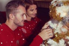 Pares jovenes que adornan un árbol de navidad Imagen de archivo