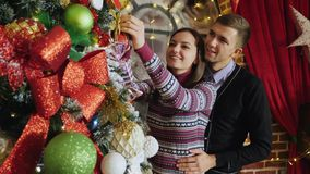 Pares jovenes que adornan un árbol de navidad en casa almacen de metraje de vídeo