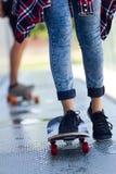 Pares jovenes que andan en monopatín en la calle Fotos de archivo