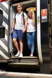 Pares jovenes que bajan del tren en la plataforma Fotografía de archivo