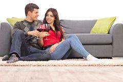Pares jovenes que beben el vino rojo Imágenes de archivo libres de regalías