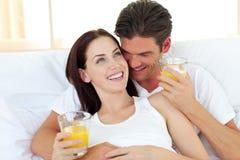 Pares jovenes que beben el zumo de naranja en su cama Fotografía de archivo