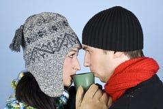 Pares jovenes que beben la bebida caliente de la misma taza Imágenes de archivo libres de regalías