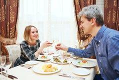 Pares jovenes que beben y que comen en el restaurante Foto de archivo libre de regalías