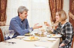 Pares jovenes que beben y que comen en el restaurante Fotos de archivo