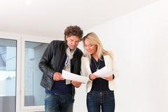 Pares jovenes que buscan las propiedades inmobiliarias Imagen de archivo libre de regalías