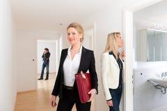 Pares jovenes que buscan las propiedades inmobiliarias con agente inmobiliario Foto de archivo libre de regalías